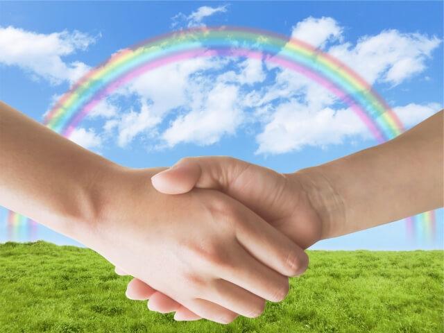 草原と青空と虹を背景に握手をする手