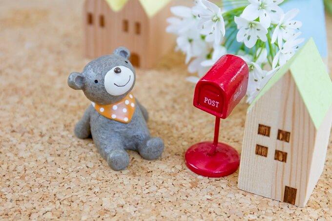 おもちゃの家とポストの横に座るおもちゃのくまさん