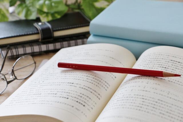 デスクの上の専門書と赤鉛筆