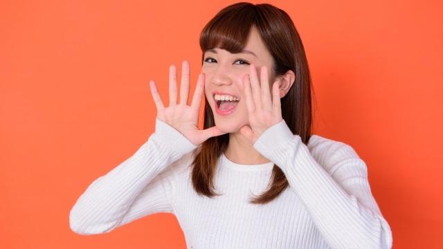 手を口に当てて叫ぶ(「ちゅーもーく!」)女性